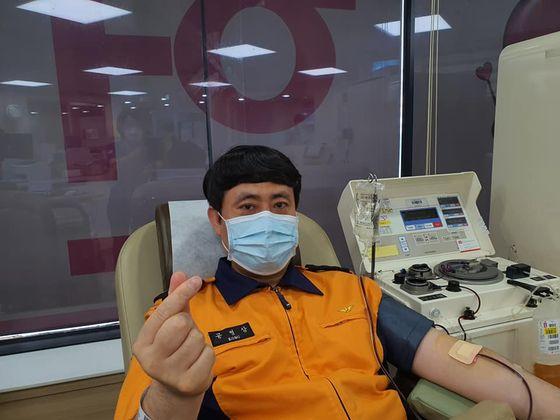 경기도 부천소방서 공병삼 소방장(왼쪽)이 헌혈 중 하트를 만들어 보이고 있다.