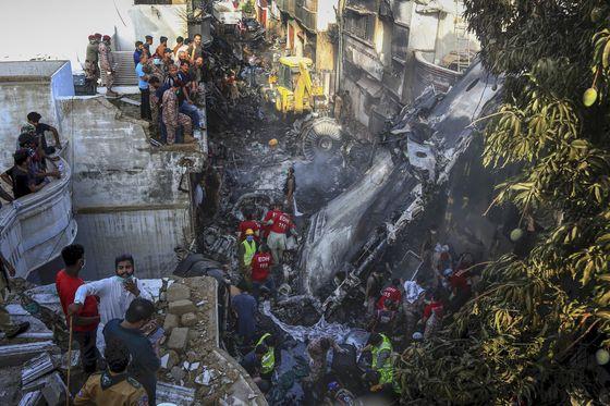 자원봉사자들이 지난달 22일 파키스탄 남부 카라치 주택가에 추락한 여객기 주변에서 생존자를 찾고 있다. AP=연합뉴스