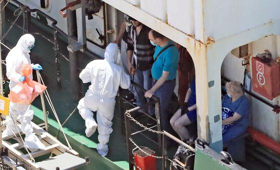 23일 오후 부산 감천항에 정박 중인 러시아 국적 냉동 화물선에서 코로나19 양성 판정을 받은 선원들이 부산의료원으로 이송되고 있다. 송봉근 기자