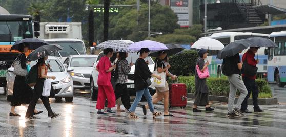 시민들과 여행객들이 우산을 쓴 채 부산 동구 부산역 앞 횡단보도를 지나고 있다. 송봉근 기자