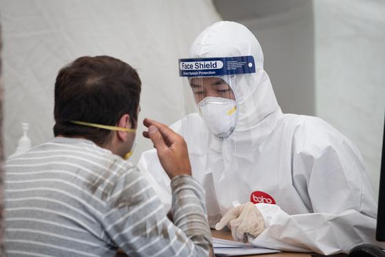 23일 서울시내 한 신종 코로나바이러스 감염증(코로나19) 선별진료소에서 방역복을 착용한 관계자들이 업무를 보고 있다.방역당국은 코로나19가 쉽게 종식되지 않을 것이라며 장기전에 들어갈 것임을 밝혔다.뉴스1