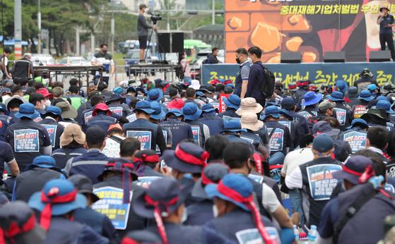지난 10일 오후 서울 여의도공원 인근에서 열린 중대재해기업처벌법 우선 입법 촉구 민주노총 결의대회에서 참석자들이 거리를 가까이 둔 채 앉아 있다. 연합뉴스