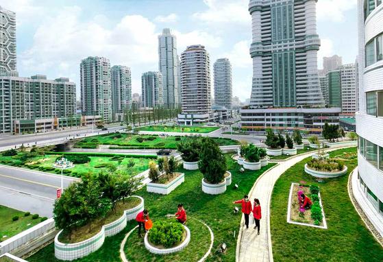 """북한 노동당 기관지 노동신문은 지난 4월 26일자에서 """"녹지와 꽃들로 이채롭게 장식된 여명거리""""라며 여명거리 전경 사진을 게재했다. 여명거리는 김정은 국무위원장 시대 들어 평양에 새롭게 만들어진 신시가지로 아파트를 비롯해 고층 빌딩들이 대거 들어서 있다. [뉴스1]"""