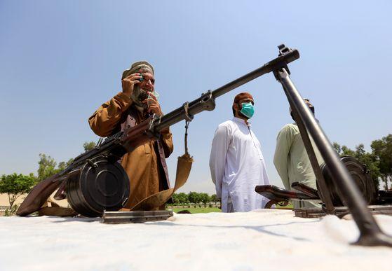 지난 25일 탈레반 조직원이 자신의 무기를 내주고 아프가니스탄 정부와 잘랄라바드 재건에 동참을 선언하고 있다. 로이터=연합뉴스