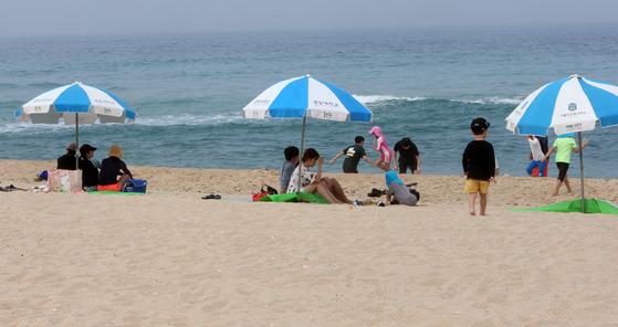 27일 오후 파라솔이 일정한 거리를 두고 설치된 강릉 경포해변에서 피서객이 휴일을 보내고 있다. 연합뉴스