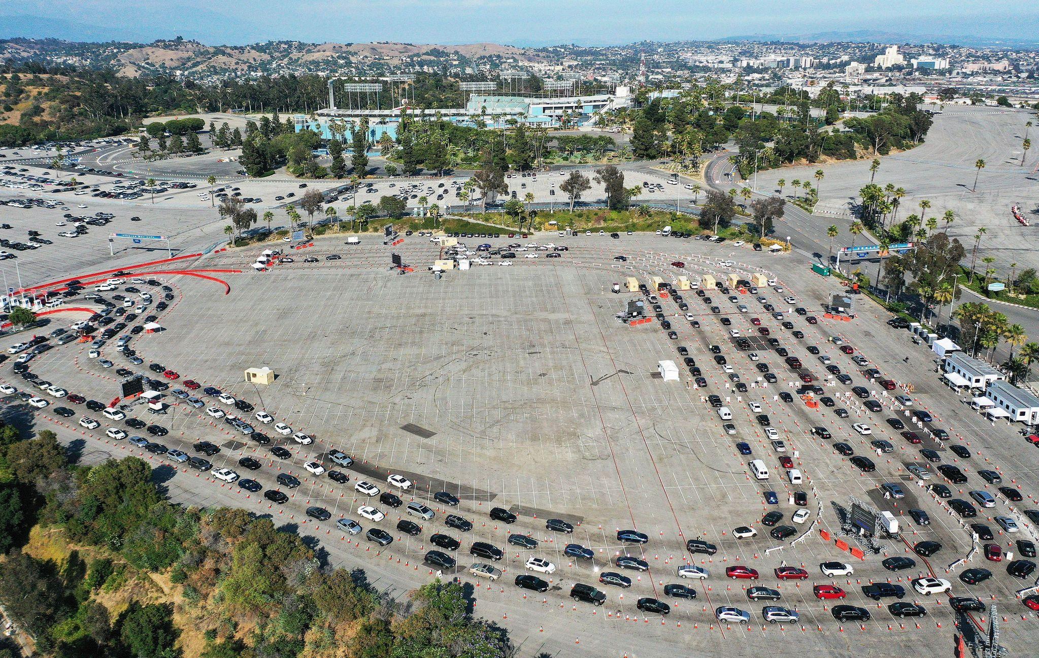 코로나19 검사를 받으려는 사람들이 탑승한 차량들이 26일(현지시간) 미국 캘리포니아주 LA 다저스 스타디움 주차장에 장사진을 치고 있다. 늘어선 차량 뒷 편에 다저스 경기장이 보인다. [AFP=연합뉴스]