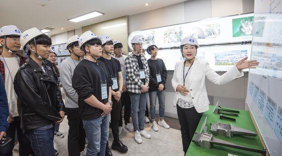 지난해 부산발전본부에서 활동한 에너지도슨트가 발전소를 방문한 대학생에게 발전설비에 대한 안내를 하고 있는 모습이다.