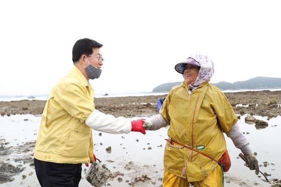 지난달 24일 충남 보령시 오천면의 섬을 방문한 양승조 충남지사가 바지락을 채취하고 있는 주민과 악수하며 환하게 웃고 있다. [사진 충남도]