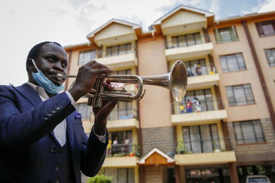케냐 나이로비의 한 아파트. 발코니에 나온 주민들을 위해 예배가 열리는 가운데 한 연주자가 트럼펫을 불고 있다. [AP=연합뉴스]
