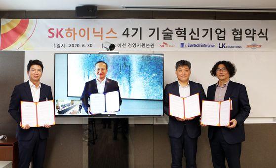 SK하이닉스가 30일 화상으로 개최한 '4기 기술혁신기업' 협약식에서 이준호(사진 왼쪽부터) ㈜엘케이엔지니어링 대표, 이석희 SK하이닉스 CEO, 한태수 ㈜에버텍엔터프라이즈 대표, 김지석 ㈜쎄믹스 대표가 기념 촬영을 하고 있다. [사진 SK하이닉스]
