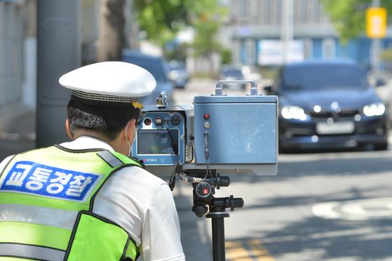 지난 1일 경북 포항북부경찰서 소속 교통경찰관이 시내 스쿨 존(어린이보호구역)에서 이동식 단속카메라로 규정 속도위반 차량을 단속하고 있다. 뉴스1