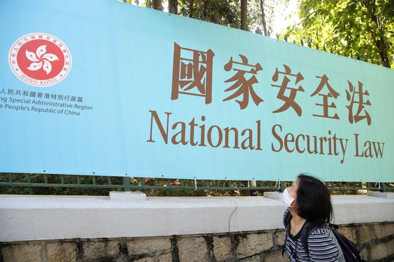 중국 전인대 상무위원회가 6월 30일 홍콩 국가보안법(국가안전법) 최종 입법을 강행한 날 한 여성이 홍보 플래카드를 쳐다보고 있다. 미국 상무부는 세 시간전 홍콩에 대한 기술 수출통제 면제조치를 박탈하면서 홍콩 특별지위 폐지 절차를 시작했다.[AP=연합뉴스]
