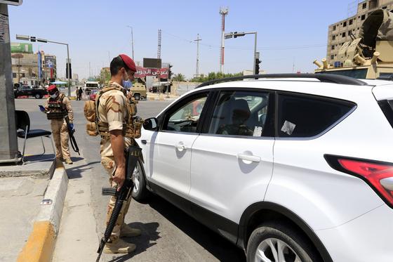 이라크 군인이 11일(현지시간) 바그다드 남부 카르바라 지역에서 차량을 타고 나온 시민에게 코로나19 관련 체크를 하고 있다. [EPA=연합뉴스]