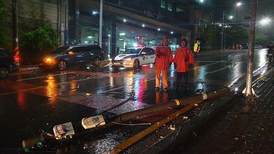 29일 오후 10시20분쯤 부산 사하구 당리동의 한 도로에 설치된 통신주가 강풍에 쓰러져 소방대원들이 안전 조치를 하고 있다. [사진 부산소방본부]