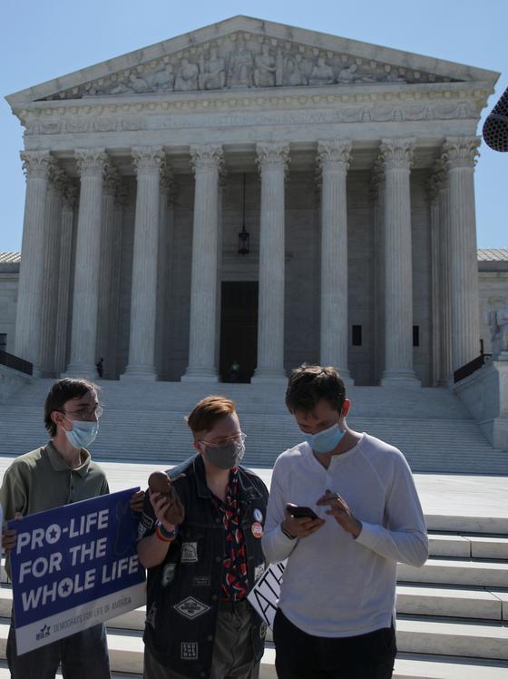 낙태 반대운동 시위대가 29일(현지시간) 미국 연방법원 앞에서 루지애나주의 낙태 의료시설법을 폐지한 대법원의 판결을 휴대전화로 읽고 있다. [로이터=연합뉴스]