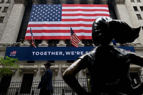 미국 뉴욕 월스트리트에 있는 증권거래소 앞 '용감한 소녀'상. 코로나19 시대를 함께 이겨내자는 플래카드가 대형 성조기와 함께 붙어있다. AFP=연합뉴스