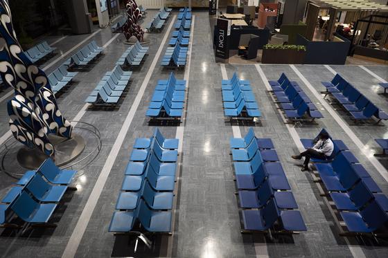 지난 4월 1일 일본 나리타국제공항 출국장 대기석에 한 남성이 앉아 있다. 일본은 현재 전 세계 129국에 대해 입국거부 조치를 하고 있다. [AP=연합뉴스]