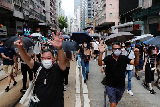 홍콩 보안법에 반대하는 시민들이 1일 거리에서 가두 시위를 벌이고 있다. 시위대는 홍콩 독립파를 상징하는 검은색 셔츠를 입고 검은 우산을 든 채 행진했다. [로이터=연합뉴스]