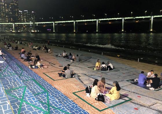 부산 수영구가 신종 코로나바이러스 감염증(코로나19) 확산을 막기 위해 지난 6월 10일부터 민락수변공원에 가로 2m, 세로 1.5m 길이로 청테이프를 붙여 구역을 나눴다. 연합뉴스
