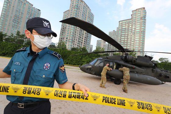 2일 오후 서울 용산구 이촌동 한강공원에서 경찰관계자가 엔진 고장으로 비상착륙한 헬리콥터 주위로 폴리스라인을 설치하고 있다. 연합뉴스