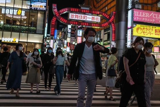 지난달 24일 마스크를 쓴 사람들이 일본 도쿄의 대표적인 유흥가인 신주쿠 가부키초 앞 횡단보도를 건너고 있다. 2일 도쿄에선 두 달 만에 100명이 넘는 코로나19 확진자가 발생했다. 유흥가를 중심으로 20~30대들의 감염 사례가 급증하고 있는 것으로 전해졌다. [AFP=연합뉴스]