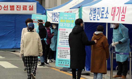 지난 3월 서울 동대문구 보건소에서 관계자들이 선별진료소를 찾은 시민을 안내하고 있다. 연합뉴스