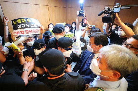 지난달 22일 인천국제공항 제1여객터미널에서 보안검색 요원들의 정규직화 관련 브리핑을 마친 구본환 인천국제공항공사 사장이 직원들의 항의를 받고 있다. 연합뉴스