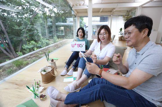 LG유플러스의 전략기획담당 박치헌 상무가 신입사원 멘토들과 서울 성수동에서 MZ세대가 찾는 문화공간을 체험하고 있다. [LG유플러스 제공]