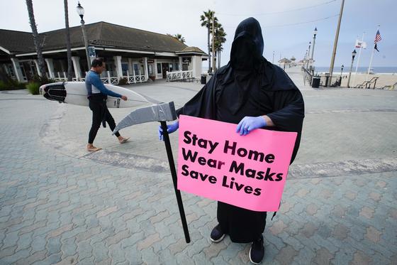 지난 5월 8일 미국 캘리포니아주 로스앤젤레스의 한 해수욕장 인근에서 '죽음의 신(grim reaper)' 복장을 한 남성이 '생명을 구하기 위해 외출을 자제하고 마스크를 쓰라'는 내용의 팻말을 들고 있다. [AP=연합뉴스]