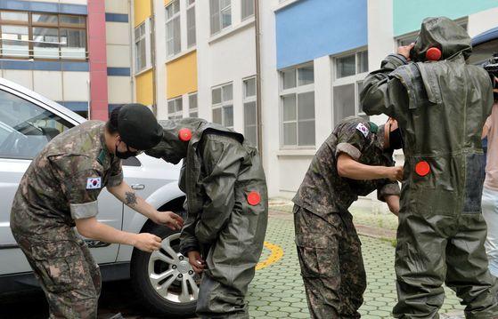 전국 첫 학교내에서 신종 코로나 바이러스 감염증(코로나19) 확진자가 발생한 2일 대전 천동초등학교에 투입된 국군화생방방호사령부 현장지원팀 요원들이 긴급 방역을 실시하고 있다. 프리랜서 김성태