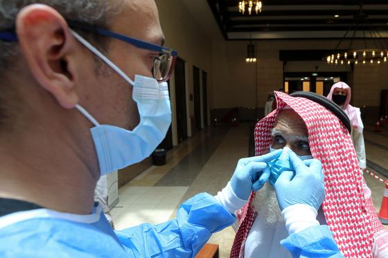 사우디아라비아에서 신종 코로나바이러스 감염증 확산세가 지속되는 가운데 모스크 앞에서 보안요원이 기도를 하러온 성도의 마스크를 확인하고 있다.[로이터=연합뉴스]