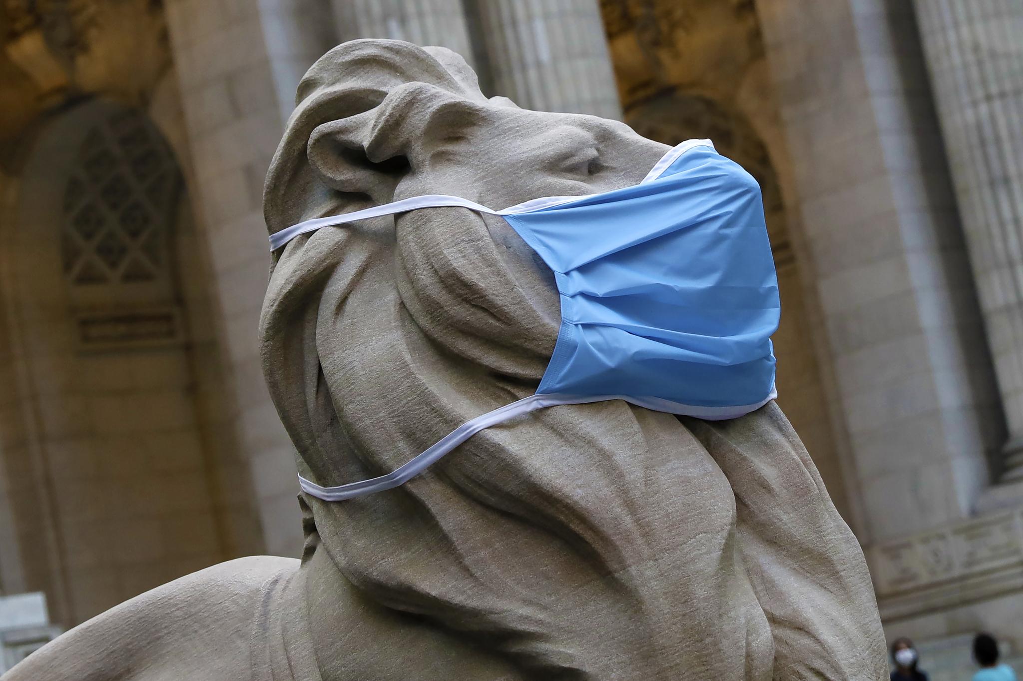 지난달 30일(현지시간) 미국 뉴욕의 공공 도서관 앞에 있는 사자상이 대형 마스크를 쓰고 있다. 사람들에게 마스크 착용의 필요성을 알리기 위해 이뤄진 변화다. [EPA=연합뉴스]