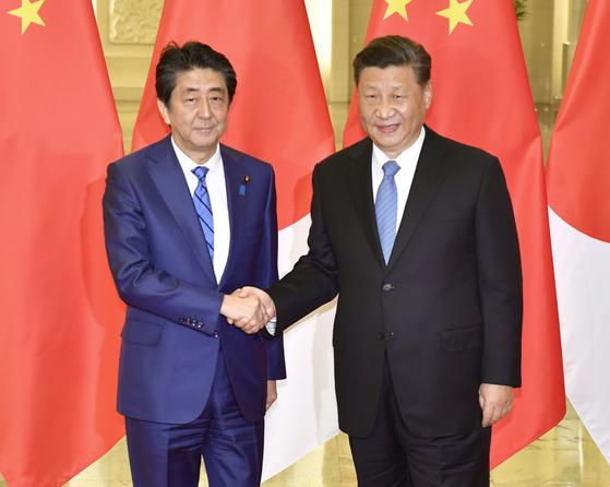 지난해 12월 중국을 방문한 아베 신조(安倍晋三) 일본 총리(왼쪽)가 베이징(北京) 인민대회당에서 시진핑(習近平) 중국 국가 주석과 정상회담을 하기에 앞서 악수하고 있다. [교도=연합뉴스]