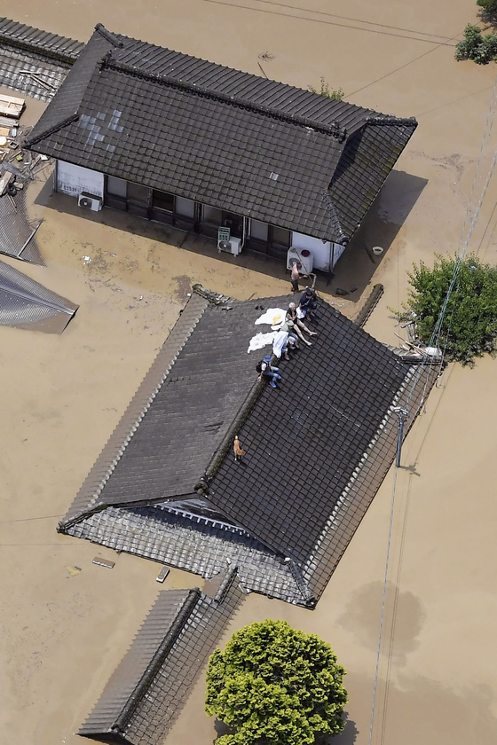 4일(현지시간) 일본 규슈 지방 구마모토현, 히토요시의 한 마을에서 주민들이 구조를 기다리고 있다. AP=연합뉴스