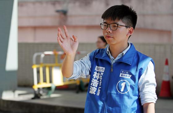 홍콩 민주화 시위의 주역인 조슈아 웡이 지난해 11월 홍콩 사우스 호라이즌스 커뮤니티센터에 설치된 투표소 인근에서 선거 유세 지원을 하고 있다. [연합뉴스]