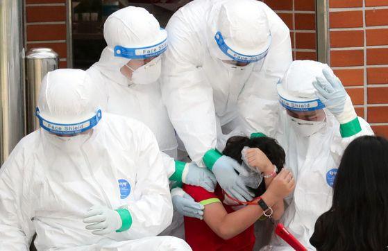 서울 중랑구의 묵현초등학교 학생 1명이 신종 코로나바이러스 감염증(코로나19) 확진 판정을 받은 5일 묵현초에 마련된 선별진료소에서 한 학생이 의료진의 도움을 받으며 검사를 받고 있다. 뉴스1