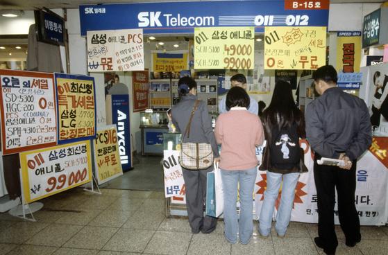 SK텔레콤의 2G 이동통신 서비스가 이달 27일 종료된다. 기존 가입자에 대해서는 휴대전화 교체를 무료로 지원하고, 011 등 번호는 내년 6월 말까지 1년 더 쓸 수 있다. 사진은 1999년 3월 011 가입자를 모집 중인 SKT 대리점의 모습. [연합뉴스]