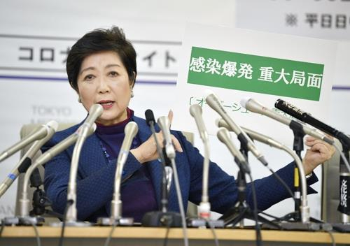 고이케 유리코 일본 도쿄도 지사가 지난 3월말 도쿄도청에서 긴급 기자회견을 하던 중 '감염폭발 중대국면'이라고 쓴 카드를 들어보이고 있다. [연합뉴스]