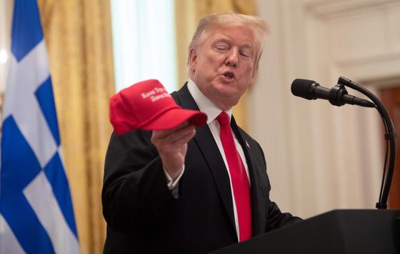 도널드 트럼프 미국 대통령이 '미국을 다시 위대하게'라고 쓴 모자를 들어보이고 있다. [AFP=연합뉴스]
