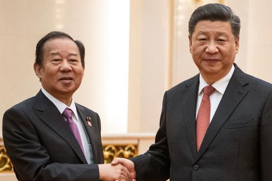 지난해 4월 24일 중국을 방문한 니카이 도시히로 자민당 간사장이 시진핑 중국 국가주석을 만나 악수하고 있다. [로이터=연합뉴스]