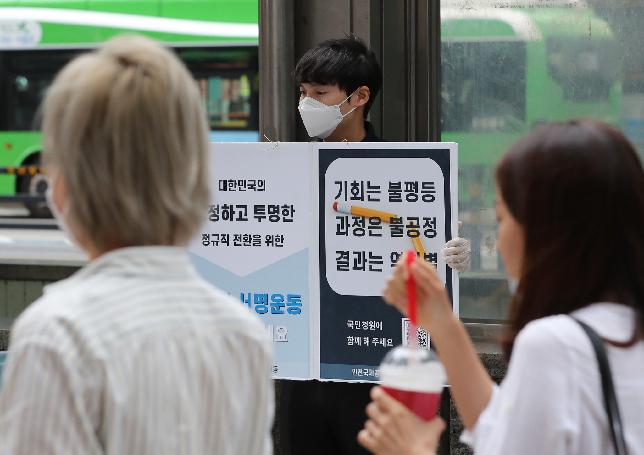 지난달 30일 서울 마포구 홍대입구역에서 인천국제공항공사 직원이 공정하고 투명한 정규직 전환을 요구하는 피켓을 들고 있다. 뉴스1