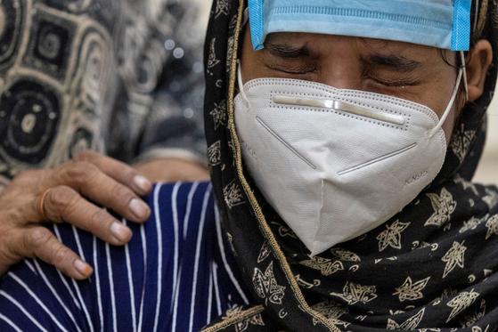 인도 뉴델리의 한 병원에서 코로나19 환자의 보호자가 환자와 영상통화를 기다리며 눈물을 흘리고 있다. [로이터=연합뉴스]