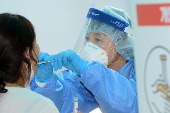 7일 오후 광주 광산구 신창동 행정복지센터에 설치된 임시 신종 코로나바이러스 감염증(코로나19) 선별진료소에서 보건소 관계자가 검체를 채취하고 있다. 뉴스1