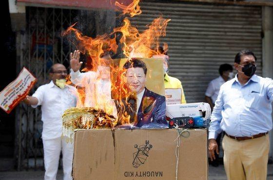 지난달 22일 인도 뉴델리 인근에서 시위대가 시진핑 중국 국가주석의 사진을 불태우고 있다.[로이터=연합뉴스]