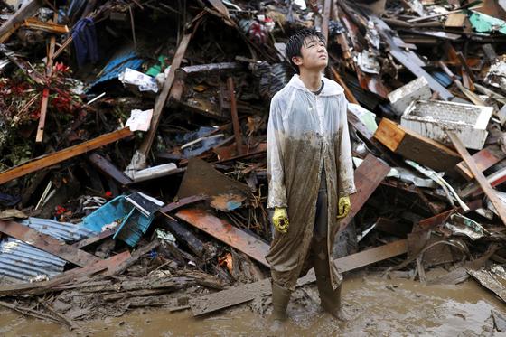 7일 일본 규슈 구마모토현 히토요시에서 한 주민이 홍수로 떠밀려온 잔해를 정리하던 도중 하늘을 올려다보고 있다. 로이터=연합뉴스