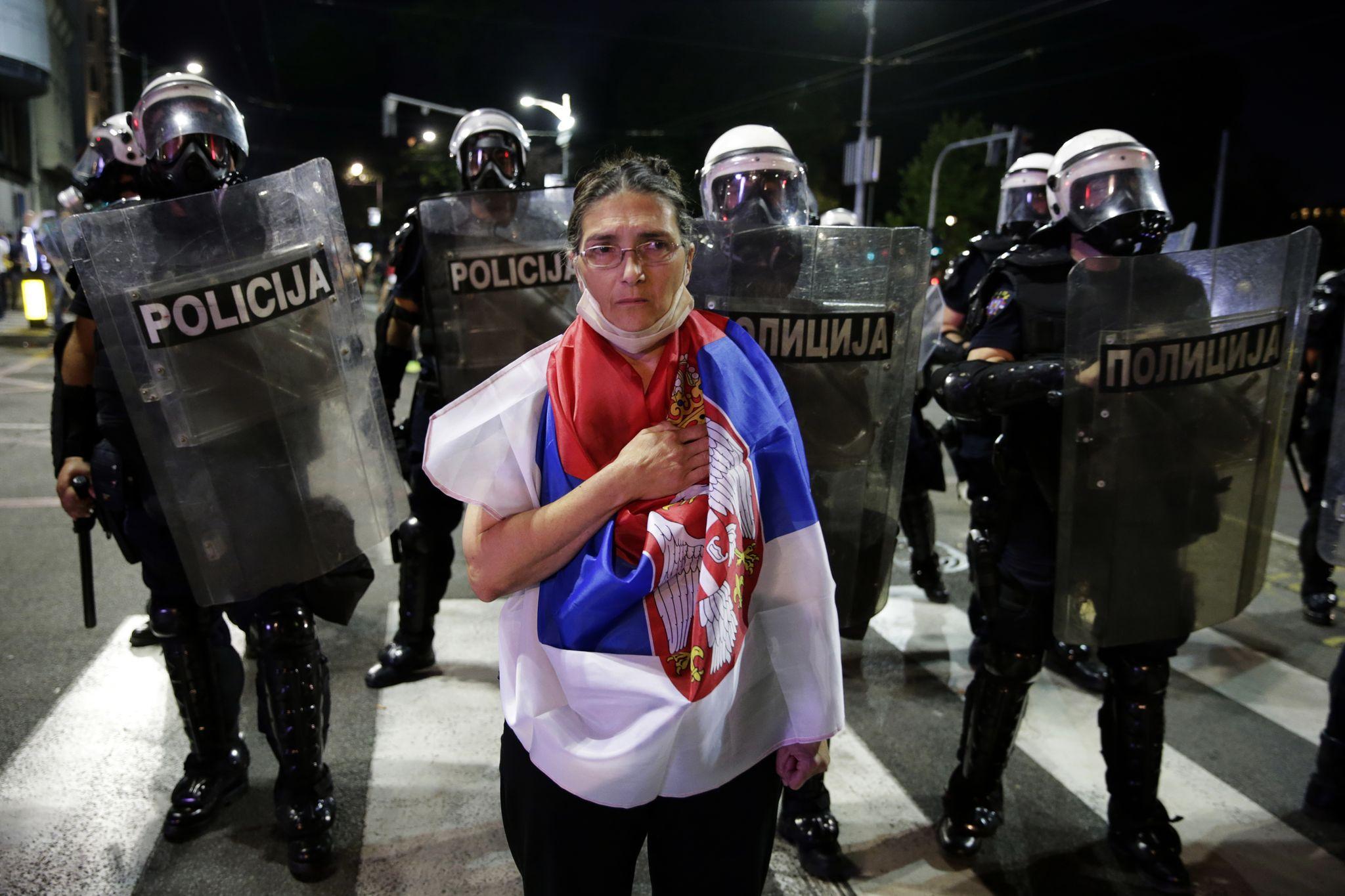 세르비아 국기로 몸을 감싼 한 베오그라드 시위대가 경찰 저지선 앞에 서 있다. EPA=연합뉴스
