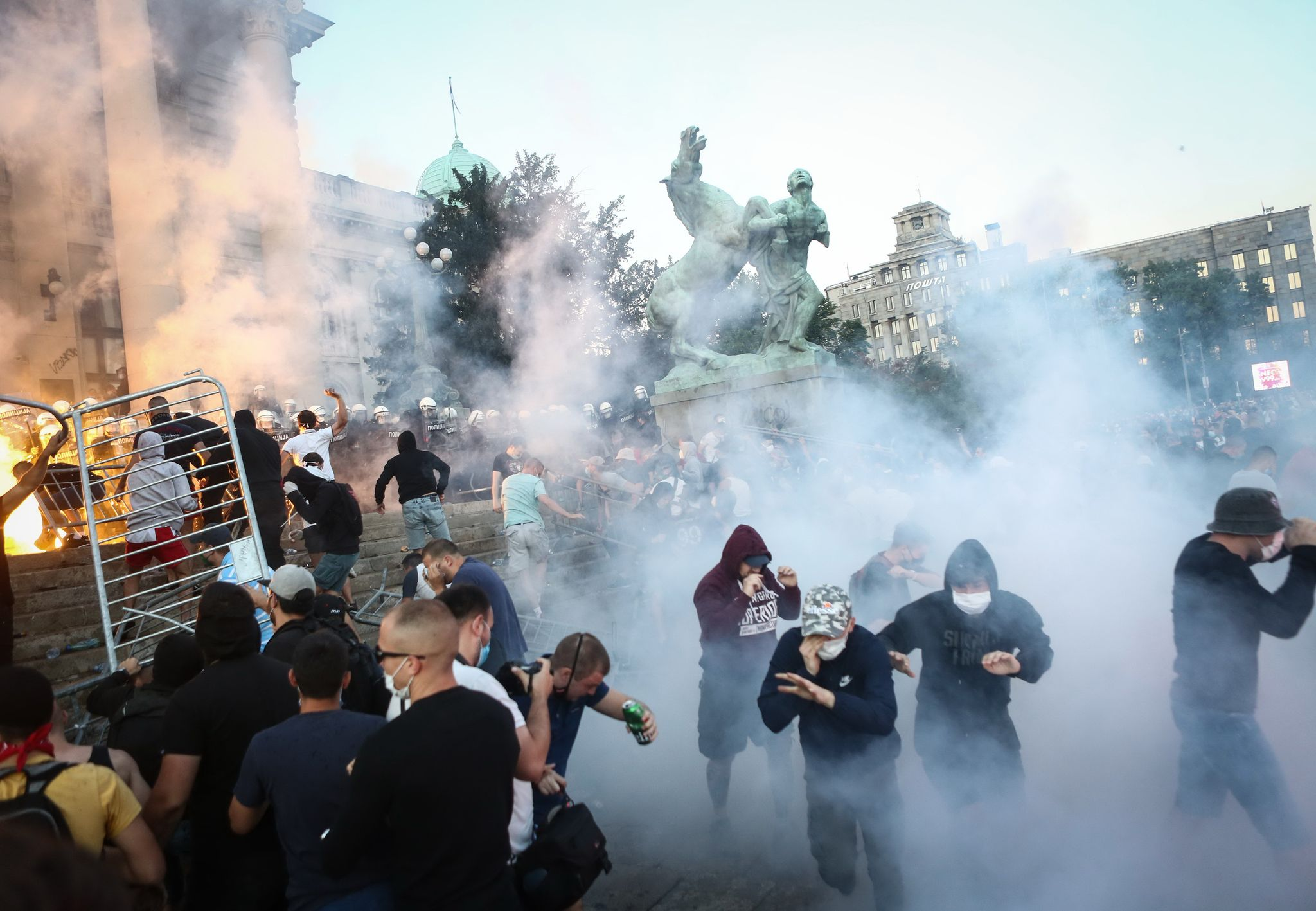 세르비아 수도 베오그라드의 반정부 시위대가 8일 의회 진입을 시도하다 경찰이 쏜 최루탄에 흩어지고 있다. AFP=연합뉴스