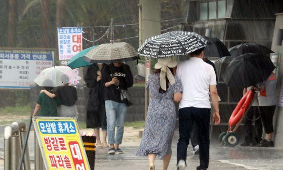 비가 내리는 7일 오후 제주시 금능해수욕장에서 관광객들이 비를 피해 발걸음을 옮기고 있다. 뉴스1