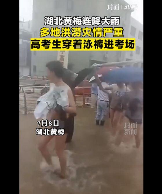 중국 후베이성 황메이현의 화닝고교 학생들이 8일 침수된 학교장에서 빠져 나온 뒤 아예 수영복을 입은 채 고사장으로 향하고 있다. [중국 펑몐신문망 캡처]