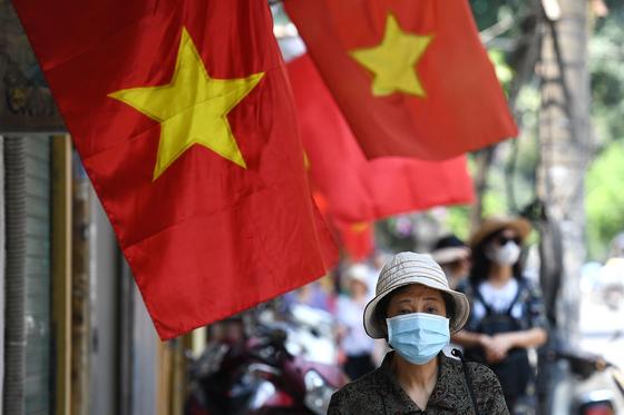 베트남 하노이에서 마스크를 쓴 여성이 베트남 국기 아래를 지나고 있다. 코로나 청정국 베트남에선 최근 디프테리아가 확산해 방역 당국에 비상이 걸렸다. [AFP=연합뉴스]